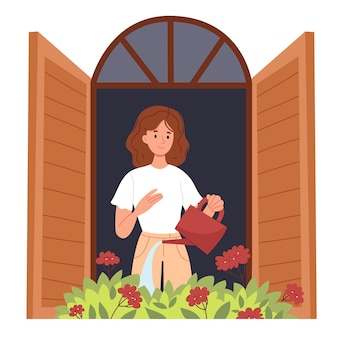 Curly girl stands on the balcony and waters the flowers with a red watering can