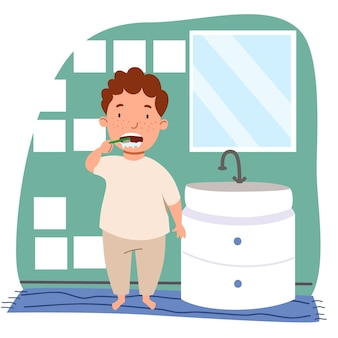 A curly-haired european boy with freckles in pajamas is brushing his teeth in the bathroom.