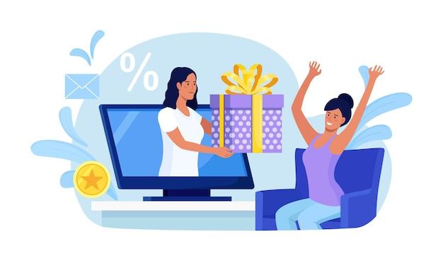 Клиент получает виртуальный подарок. женщины дают подарочную коробку с экрана компьютера. онлайн покупки. бонус, скидка, акция, программа лояльности