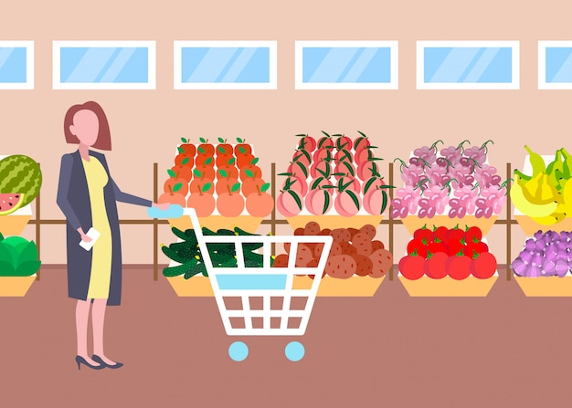 Customer woman holding trolley cart buying fresh organic fruits vegetables modern supermarket shopping mall interior female cartoon character full length flat horizontal