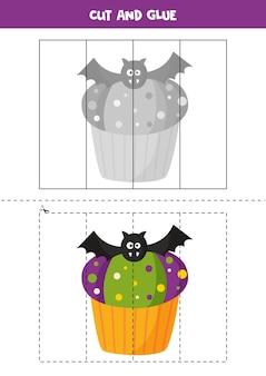 不気味な黒いバットでかわいいハロウィーンのカップケーキをカットして接着します。子供のための教育ゲーム。切ることを学ぶ。子供のためのパズル。