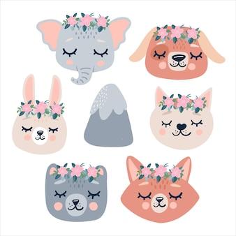 かわいい動物の頭は花輪で目を閉じてアイコンに直面しています。漫画の面白いキャラクターと山。