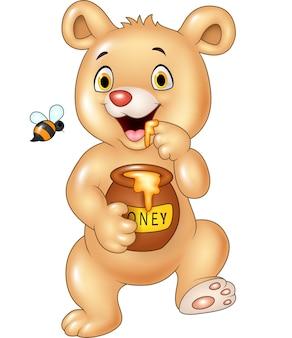 Cute baby bear holding honey pot