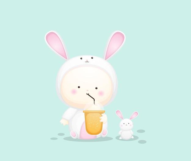 Cute baby in bunny costume holding boba. cartoon illustration premium vector
