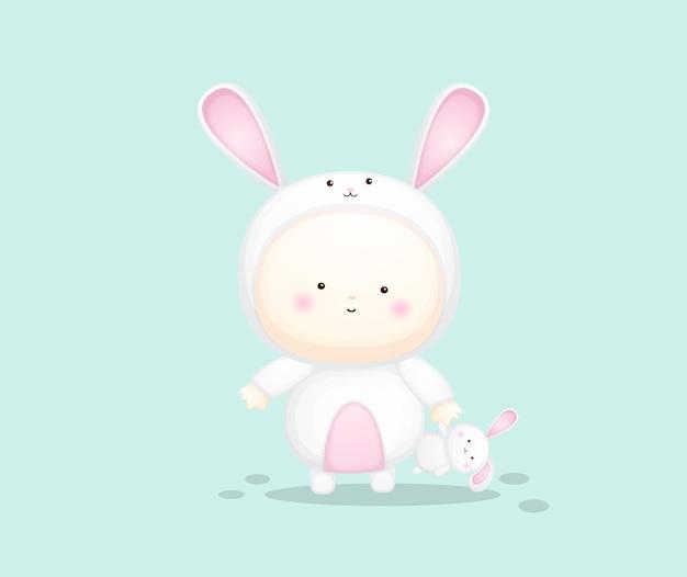 Cute baby in bunny costume holding rabbit doll. cartoon illustration premium vector