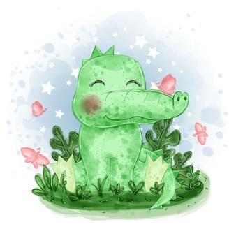 귀여운 아기 악어는 잔디에 나비와 함께 압수됩니다