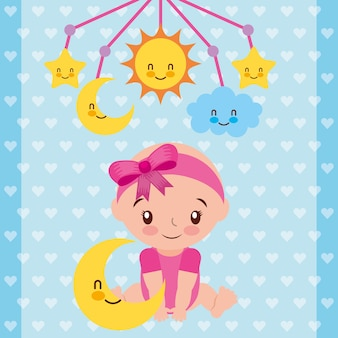 Cute baby girl sitting with star and crib mobile