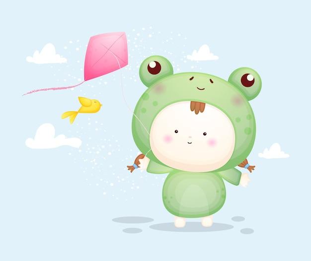 Милый ребенок в костюме лягушки, играя воздушных змеев. мультяшный талисман premium векторы