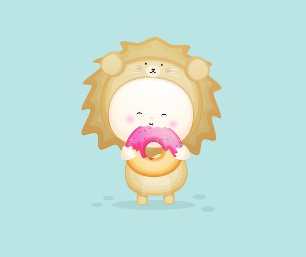 Cute baby in lion costume holding donut. mascot cartoon illustration premium vector