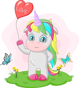 Cute baby unicorn holding red heart balloon in the grass