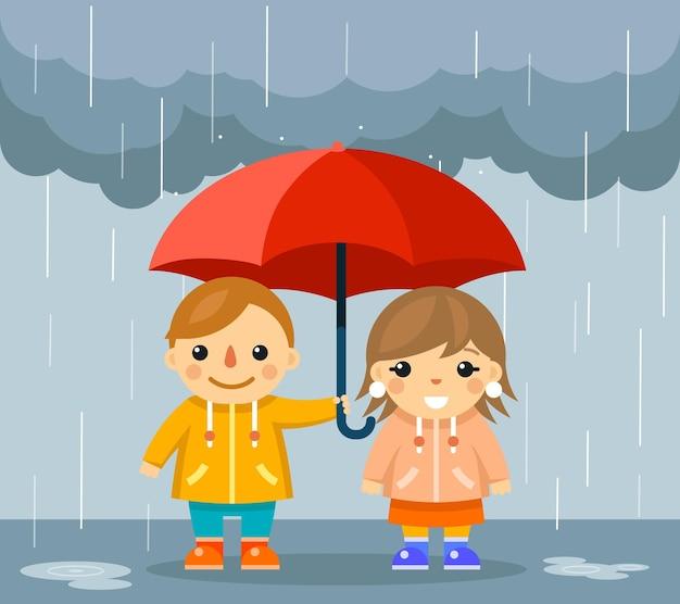 Милый мальчик и девочка с зонтиком, стоя под дождем.