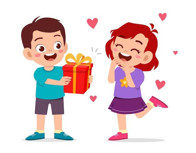 かわいい男の子は誕生日を祝うために小さな女の子にプレゼントを与える