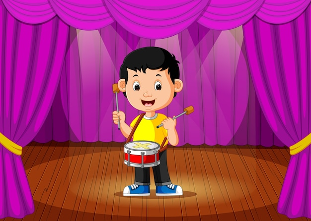 Cute boy playing drum on stage