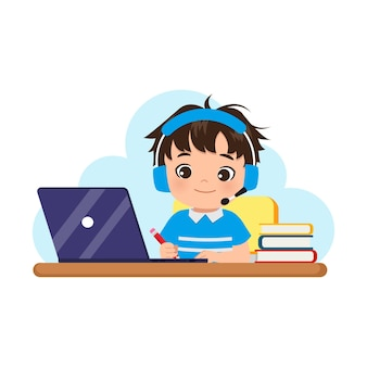 Cute boy wearing headphones learning at home with his laptop