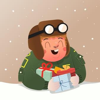 파일럿 의상 스웨터를 입은 귀여운 소년은 크리스마스 이브를 축하하고 많은 선물을 받았습니다