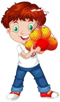 Милый мальчик с рыжими волосами держит фрукты в стоячем положении