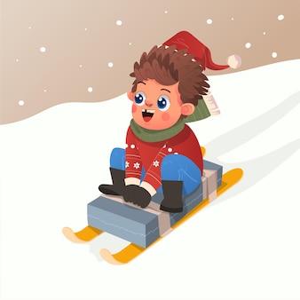 クリスマスイブを祝うために雪の中で自家製そりを再生する赤いセーターとかわいい男の子