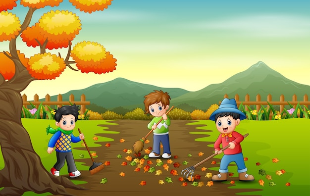 Cute boys volunteers cleaning up autumn leaves in the park