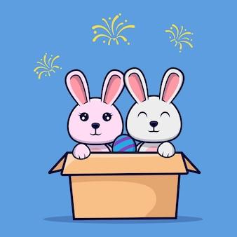 イースターエッグと段ボールの中のかわいいウサギのカップル