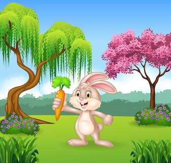 Cute bunny holding carrot in the jungle