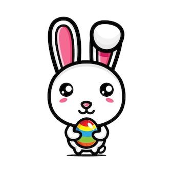 Милый кролик обнимает пасхальные яйца