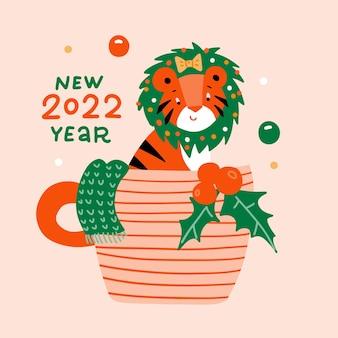 귀여운 만화 호랑이 새끼는 그의 머리에 야생 고양이 차와 함께 크리스마스 화환을 들고 커피 한 잔에 앉아 있습니다.