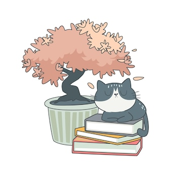 Милый кот сидит на книгах под деревом