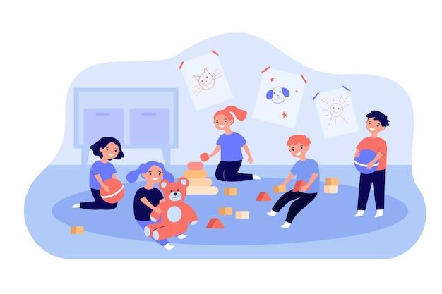 Симпатичные дети, играющие с игрушечными кубиками, шарами и плюшевым мишкой в детском саду.