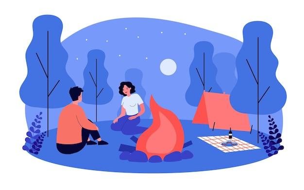夜のキャンプ場でピクニックデートをしているかわいいカップル。キャンプファイヤーフラットベクトルイラストのそばに座っているボーイフレンドとガールフレンド。キャンプ、関係、バナーの野外活動の概念、ウェブサイトのデザイン