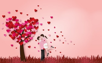 かわいいカップルは、ハートの木の芝生の床にお互いを抱擁