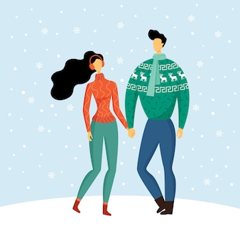 Cute couple in warm cozy sweaters holding hands, enjoying the love and snowy winter.