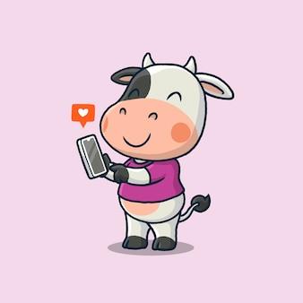 ピンクで隔離の携帯電話を保持しているかわいい牛