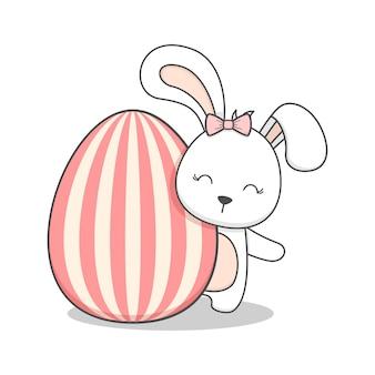 Cute easter bunny behind an egg