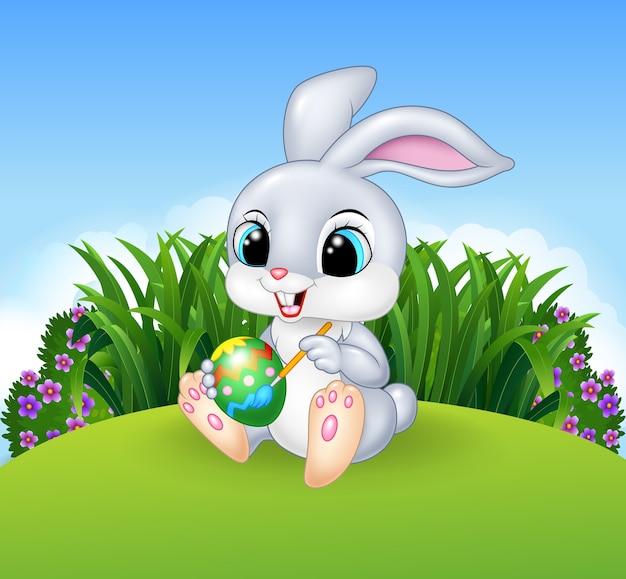 かわいいイースターバニー、牧草地の背景に卵を描く