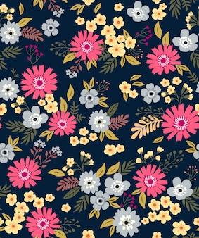 小さな色とりどりの花のかわいい花柄。シームレスなテクスチャ。青い背景。