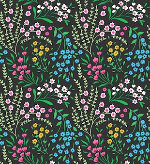 小さな色とりどりの花のかわいい花柄。シームレスなテクスチャ。緑の背景。