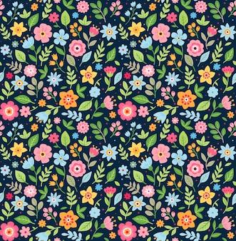 小さな花のかわいい花柄。ちっぽけなプリント。モチーフはランダムに散らばっています。シームレスなテクスチャ。ファッションプリントのエレガントなテンプレート。小さな色とりどりの花で印刷。紺色の背景。