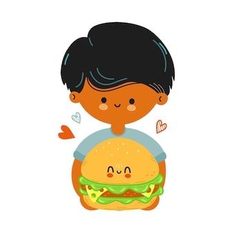 かわいい面白い男の子はハンバーガーを手に持っています