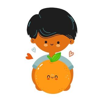 かわいい面白い男の子は、オレンジ色の果物を手に持っています