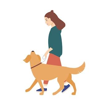 Милая забавная молодая женщина, одетая в повседневную одежду, гуляет с собакой на поводке