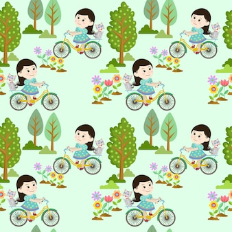 Cute girl on bicycle with cat in garden.