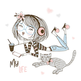Cute girl in headphones listening to music next to a pet cat.
