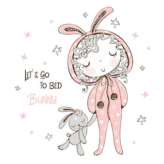 Cute girl in pajamas in the form of a bunny is going to sleep with a toy.