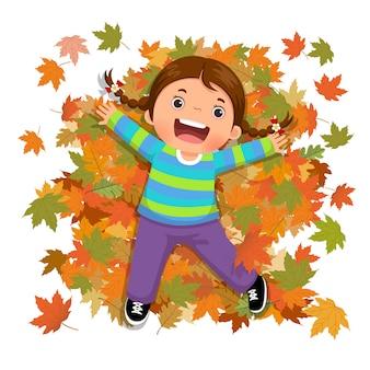 Милая девушка играет с падающими листьями