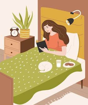 잠자기 전에 침대에서 책을 읽는 귀여운 소녀 고양이와 침실 인테리어에 젊은 여자
