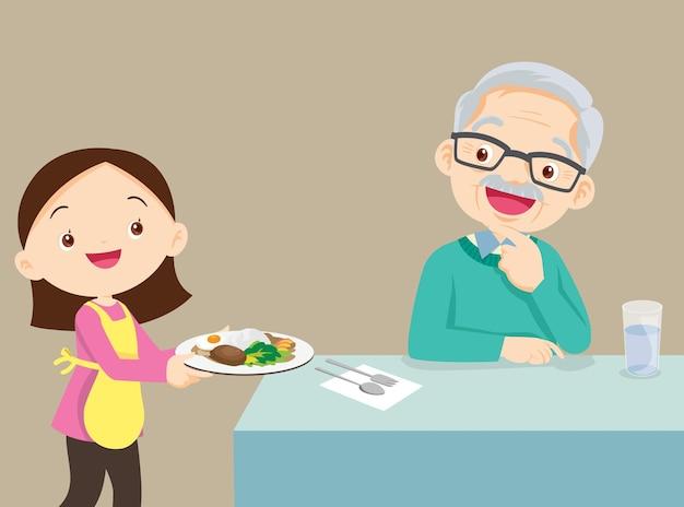年配の先輩の祖父に食べ物を提供するかわいい女の子。幸せな家族の料理。