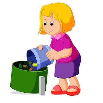 Симпатичная девушка с мешком для мусора рядом с контейнером для мусора