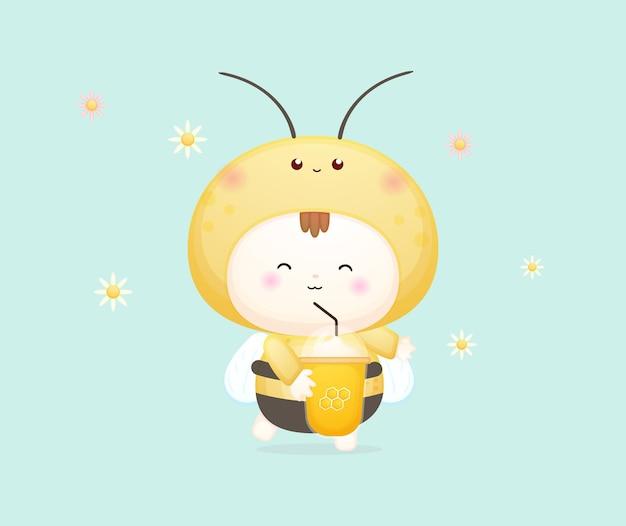 꿀벌 의상을 입은 귀여운 행복한 아기가 꿀을 들고 마십니다. 마스코트 만화 일러스트 프리미엄 벡터