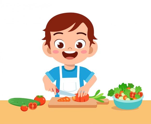 Cute happy kid cutting vegetables