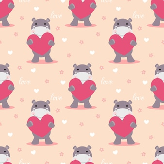 Cute hippo hold a pink heart seamless pattern.